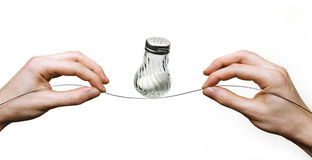 Hands balancing salt shaker on wire Stock Photos