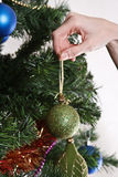 Hands with ball adorning chritmas tree Royalty Free Stock Photos