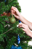Hands with ball adorning chritmas tree Stock Photo