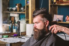 Hands of barber with clipper and comb, close up. Hipster bearded client getting hairstyle. Barbershop concept. Barber stock images