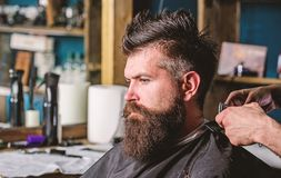Hands of barber with clipper and comb, close up. Hipster bearded client getting hairstyle. Barbershop concept. Man with stock images