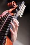 Hands on a Baroque musical instrument. Hands of a nyckhelharpor playing this handcrafted ancient traditional Swedish musical instrument, used in a folk concert Stock Images