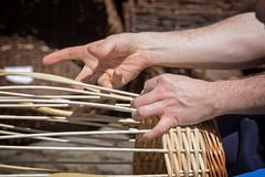 Hands of a basket maker are braiding a wicker basket. Selected focus Stock Photography