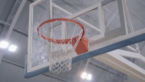 Hands of basketball player throw the ball in the basket, it goes through. Professional basketball game player in action. Concept of sport, victory stock video