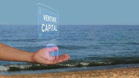 Hands on beach hold hologram text Venture Capital. Male hands on the beach hold a conceptual hologram with the text Venture Capital. A man with a holographic stock video footage