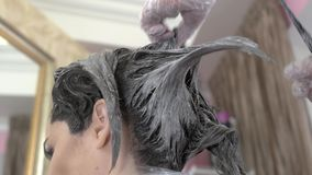 Hands of beautician dying hair. Hair care at beauty salon stock footage