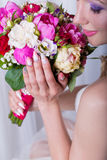 Hands beautiful delicate bride smiling girl with a large bouquet of bright color Stock Photo