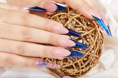 Hands with beautiful long artificial blue french manicured nails. And Christmas ball Royalty Free Stock Photography