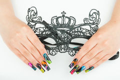 Hands with beautiful manicure holding a black lace carnival mask on white background. Hands with beautiful manicure holding a black lace carnival mask Royalty Free Stock Images