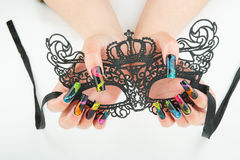 Hands with beautiful manicure holding a black lace carnival mask on white background Royalty Free Stock Images