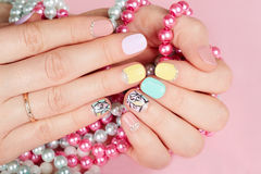 Hands with beautiful manicured nails holding colorful necklaces Stock Photos