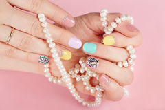 Hands with beautiful manicured nails holding pearl necklace. Hands with beautiful manicured nails different colored with nail polish  holding pearl necklace Stock Photo