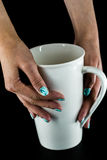 Hands with beautiful nails holding a Cup. Hands and beautiful nails on a black background with white large Cup Stock Photography