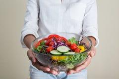 hands of beautiful woman holding big bowl of fresh veggie salad Royalty Free Stock Photos