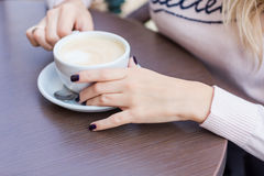 Hands of beautiful young girl holding coffe cup. Royalty Free Stock Photography