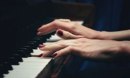 Hands of a beautiful young woman playing the piano. side view.  selective focus. copy spaceBlur royalty free stock image
