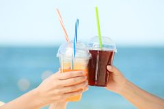 Hands of beautiful young women with drinks at sea Royalty Free Stock Image