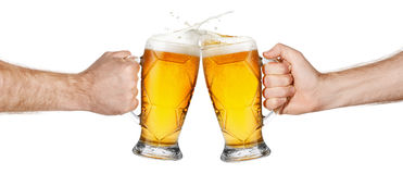 Hands with beer mugs making toast stock image