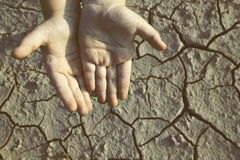 Hands begging gesture. Hands outstretched in a gesture of help. Dry earth in the background stock images