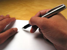 Hands beginning to write. Close-up of hands beginning to write on white paper Stock Image