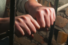 Hands behind the bars Stock Photos