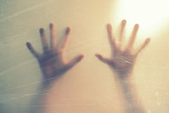 Hands behind frosted glass. depression, fear, panic, scream concept. Closeup photograph of hands behind frosted glass Royalty Free Stock Photos