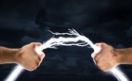 Hands bending lightning bolt stock photos
