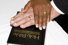 Hands on a bible. A multi racial marriage ceremony, crossed hands on a bible Stock Photos