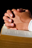 Hands on Bible. A close up of a pastor praying with his hands on the Holy Bible Royalty Free Stock Photo