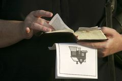 Hands and Bible. Preacher hands holding a bible and program Royalty Free Stock Photo