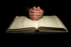 Hands on bible Stock Images