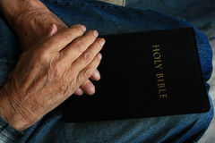 Hands on the Bible Stock Photos