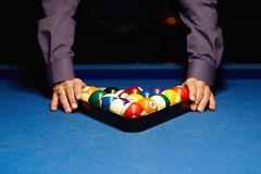 Hands on billiard balls. Man places billiard balls on the table Stock Image