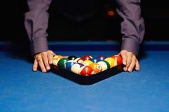 Hands on billiard balls. Man places billiard balls on the table stock image