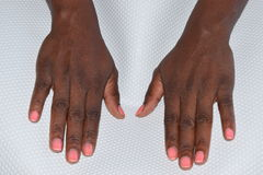 Hands of an black African woman with pink nail polish on white background Stock Photos