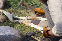 Hands of a blacksmith hammering nail using ancient tools Stock Images