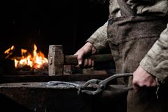The hands of a blacksmith at work in the smithy Royalty Free Stock Photos