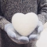 Hands in knitted mittens holding white heart. Hands in blue knitted mittens holding white heart Royalty Free Stock Image