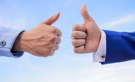Hands on blue sky background. Male hands show thumbs up sign. Success and approval concept. Gesture expresses approval. Business approval and agreement gesture stock photography