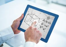 Hands with blue tablet showing black math doodles against grey interface Royalty Free Stock Image