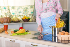 Hands and Body of Woman cooking Pasta reading Recipe Royalty Free Stock Images