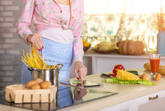Hands and Body of Woman cooking Pasta reading Recipe Stock Photography