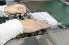 Hands on book foil packaging laminator in print plant. Production Royalty Free Stock Photo