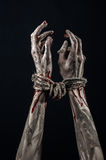 Hands bound,bloody hands, mud, rope, on a black background, isolated, kidnapping, zombie, demon Stock Image