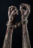 Hands bound,bloody hands, mud, rope, on a black background, isolated, kidnapping, zombie, demon Royalty Free Stock Photo