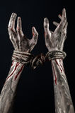 Hands bound,bloody hands, mud, rope, on a black background, isolated, kidnapping, zombie, demon. Hands bound,bloody hands, mud, rope, on a black background Royalty Free Stock Images
