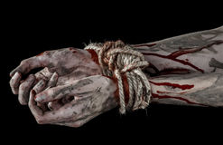 Hands bound,bloody hands, mud, rope, on a black background, isolated, kidnapping, zombie, demon. Hands bound,bloody hands, mud, rope, on a black background Stock Images