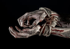 Hands bound,bloody hands, mud, rope, on a black background, isolated, kidnapping, zombie, demon. Hands bound,bloody hands, mud, rope, on a black background Royalty Free Stock Photography