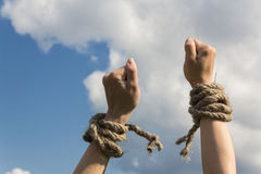 Hands bound by rope. Tied with a rope hands on blue sky background Stock Photo