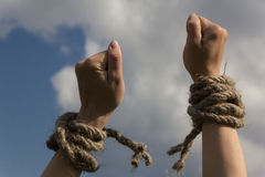 Hands bound by rope. Tied with a rope hands on blue sky background Royalty Free Stock Photos